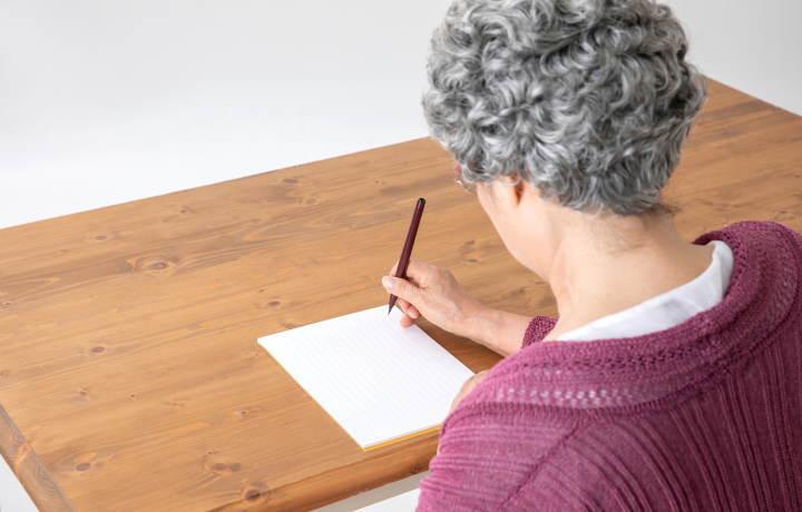 文書を書くシニア女性